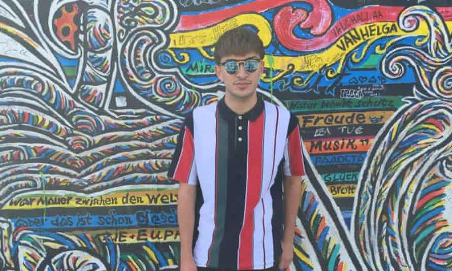 Martin in sunglasses standing in front of a wall of graffiti