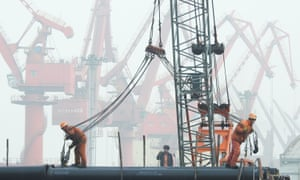 Workers prepare to load pipes onto a ship at the port in Lianyungang, China