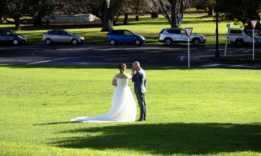 A bride and groom pose for a photo in an Auckland park
