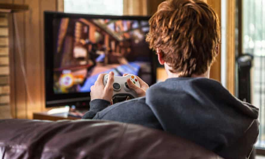 A teenager playing video games at home.