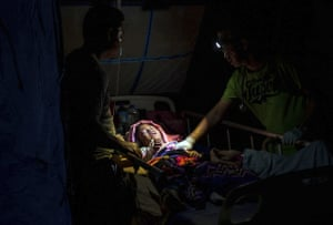 A doctor examines children injured in the earthquake at a makeshift hospital in Tanjung on Lombok Island.