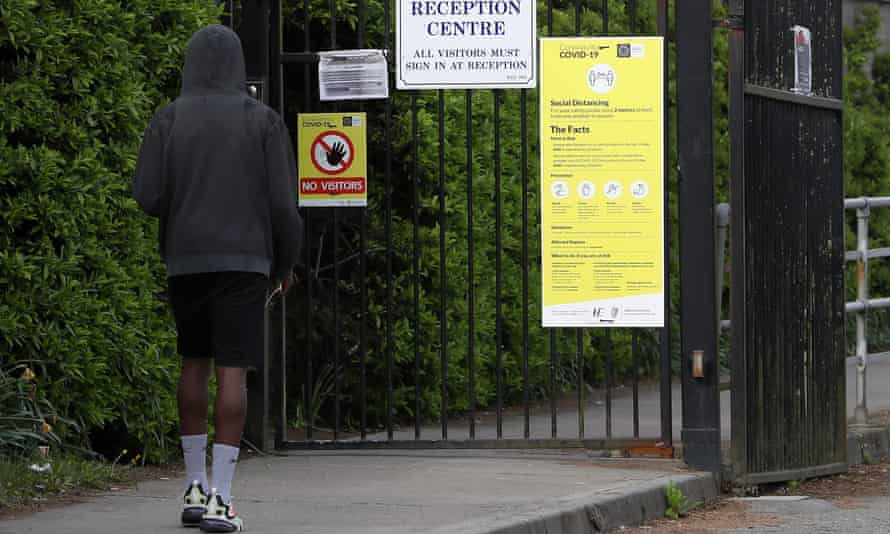 Man at the gate of a reception centre for asylum seekers
