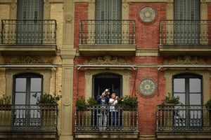 A young boy plays his trumpet from a balcony in Pamplona