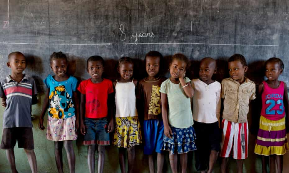 Children at Betesda primary public school, near Morondava, stand underneath a chalk line that illustrates how tall eight year olds should be.
