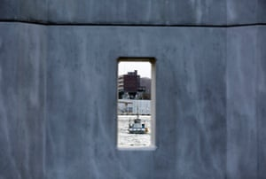 A fishing boat is seen through a window of a sea wall at a port in Miyako, Iwate prefecture