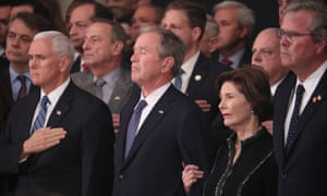 Mike Pence, George W Bush and Laura Bush watch as the casket of George HW Bush arrives to lie in state in the US Capitol.
