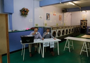 In a latherA presiding officer and poll clerk drink a cup of tea while waiting for early morning voters at a polling station set up in a launderette in Headington outside Oxford
