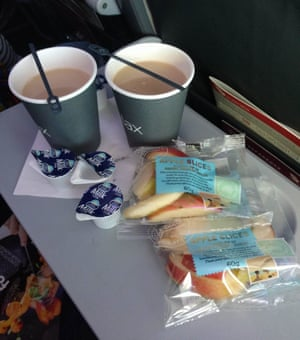 On a Virgin flight: plastic stirrer, single serve milk, plastic cup and a sliced apple covered in plastic