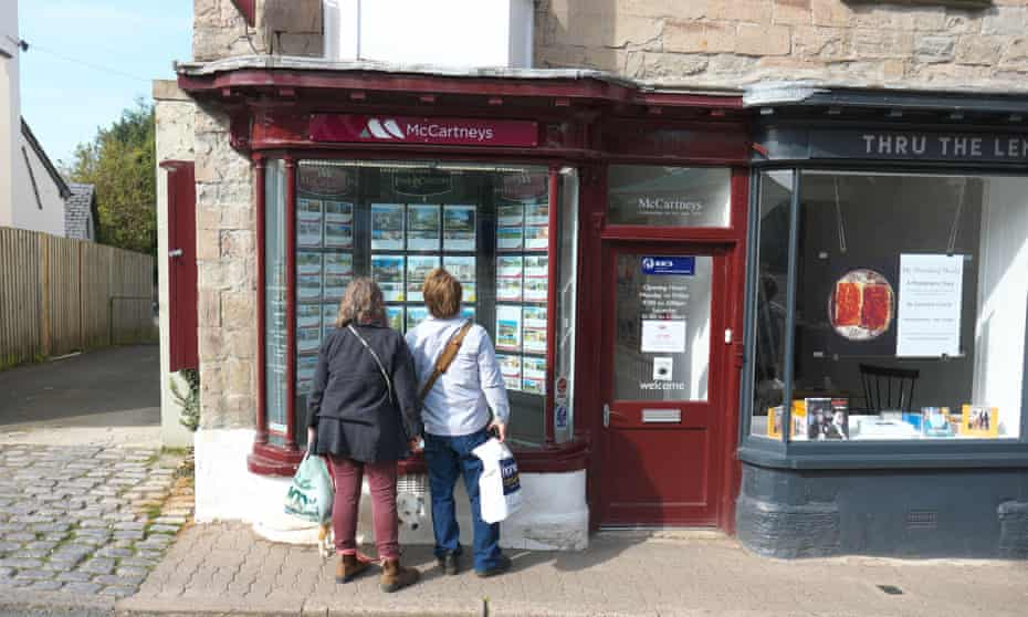 Two women looking in estate agents window