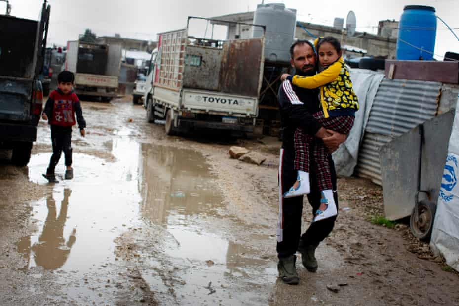Adnan Al Hussein carries his eight-year-old daughter Nada, who is no longer able to walk, through the settlement where they live in Zahle