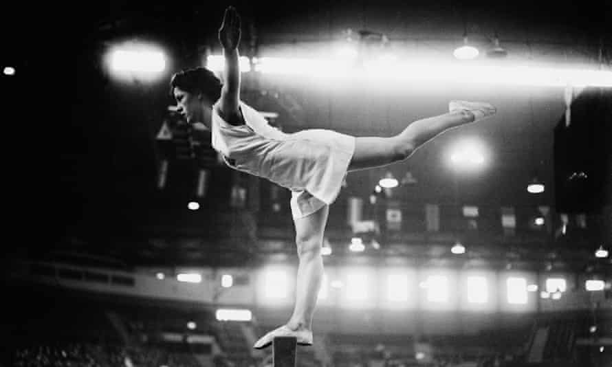 Black and white photo: a young woman balances on one leg on a bar, body horizontal, left leg stretched out behind her, arms outstretched. She wears a white singlet top and shorts, and thin slipper shoes.