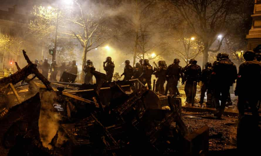 Riot police walk past burnt chairs and tables, during a protest of gilets jaunes (yellow vests).
