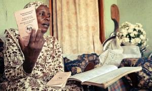 Bahati Kisenyi con la libreta de ahorros que pertenece a los miembros de la cooperativa