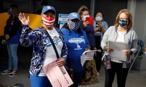 First-time voter and new US citizen Salvadora Martir, left, waves to onlookers after casting her ballot at Dodger Stadium in Los Angeles, California.