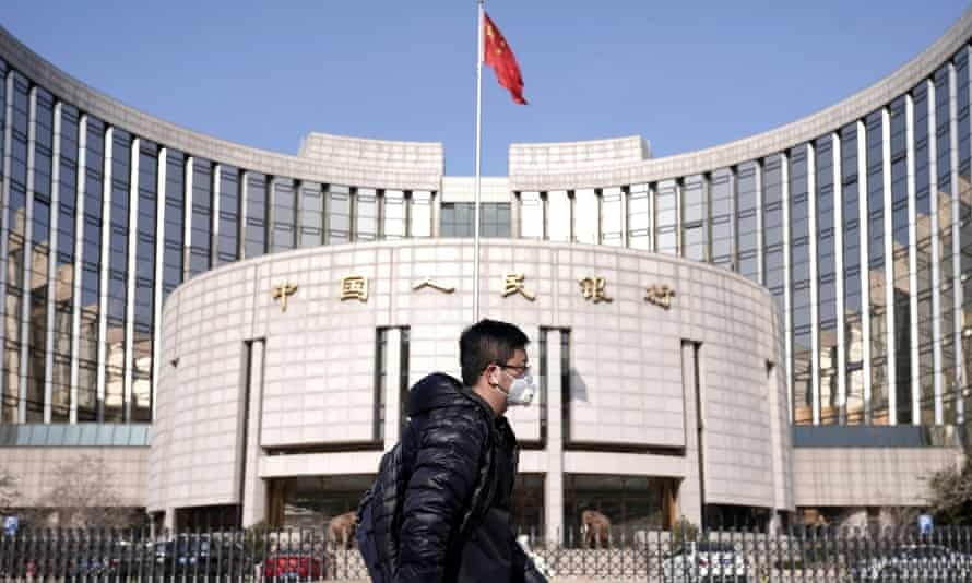 Man wearing a mask walks past the headquarters of the People's Bank of China in Beijing.