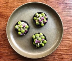 Chef Merlin Labron-Johnson's squid ink tarts with smoked cod's roe, fresh peas and chive flowers.