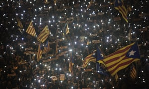 Supporters of Catalan independence wave lights and flags at a march in Barcelona on Saturday