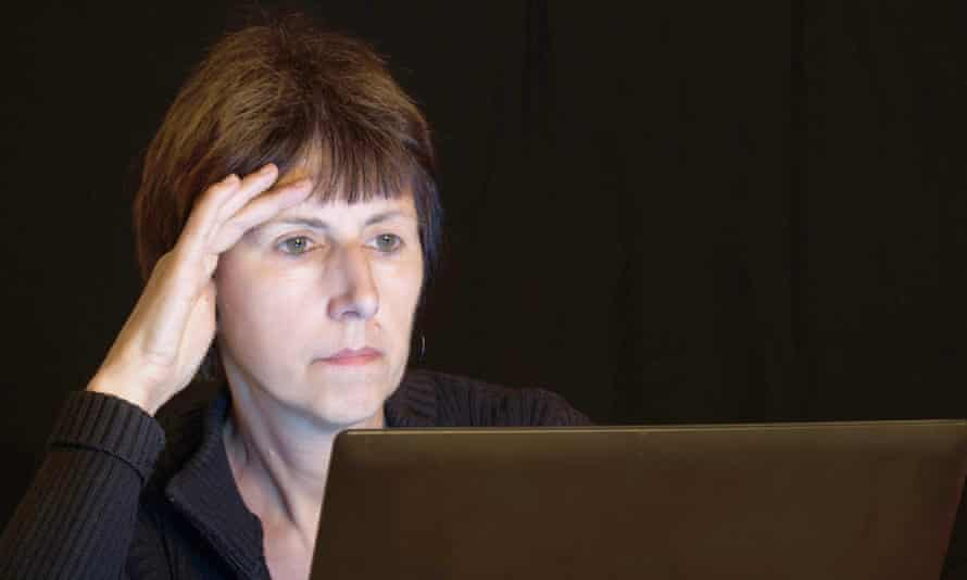 Stressed older woman with short hair, staring at a computer screen