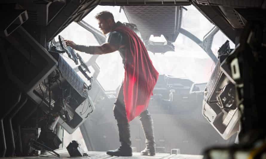 Man in a red cape inside a metal machine