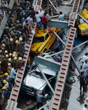 Indian rescue workers and volunteers try to free people trapped under the wreckage of the flyover.