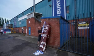 A fan places a scarf on a coffin outside Bury's Giggs Lane stadium in late August.
