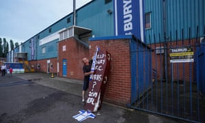 A supporter places a scarf on a coffin at Bury's Gigg Lane
