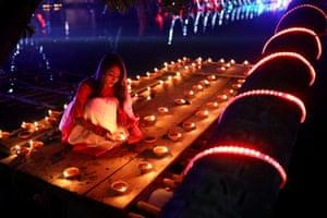 A devotee lights oil lamps in Dhaka, Bangladesh