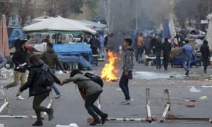 Civilians run away from teargas as Kurdish protesters clash with Turkish riot police.