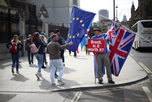 Passers by react as an anti-Brexit demonstrator waves flags outside the Houses of Parliament, in London, Britain, 10 September