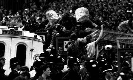 Crowds of Liverpool supporters try  to escape the crush on the Leppings Lane terrace