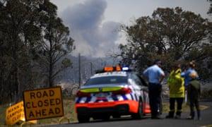Smoke from a large bushfire is seen from a roadblock outside Wytaliba, near Glen Innes, on Sunday