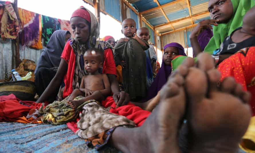 A Somali woman sits with her children inside the shelter at the Al-cadaala camp in Mogadishu