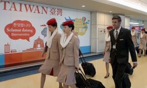 Emirates cabin crew walk past a sign at Taoyuan airport