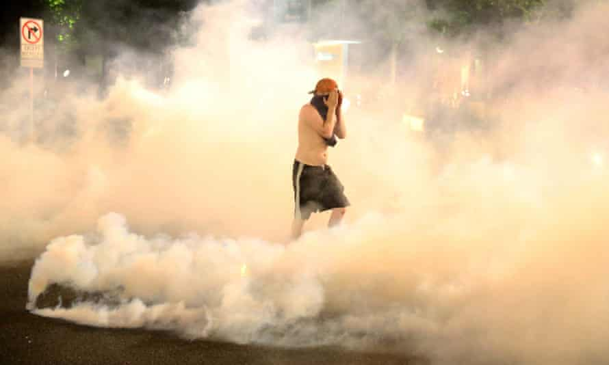 A demonstrator covers his face as teargas envelops him during protests in Portland, Oregon, on 29 March.