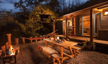 Night time exterior shot of a Devon Dens cabin with outdoor seating and firepit.