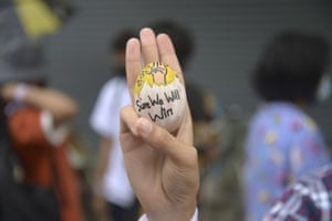 Anti-coup protester raises a decorated Easter egg along with the three-fingered symbol of resistance
