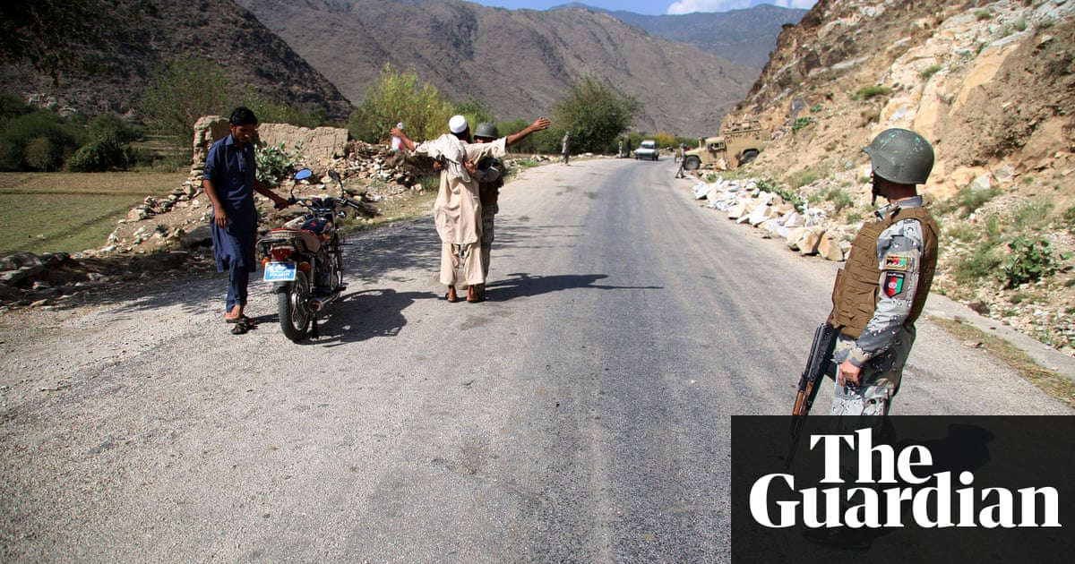 Afghan Security Officials Stand Guard On A Highway Near The Area Where US Drone Strike