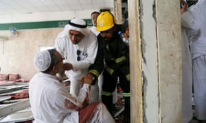 People help a man wounded in a suicide attack on the Shia Imam Ali mosque during Friday prayers.
