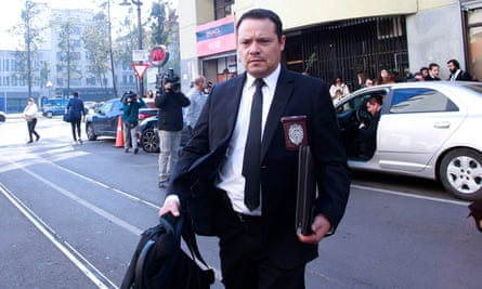 A member of the criminal investigations police leaves the Chilean Episcopate in Santiago, during a raid on Tuesday.