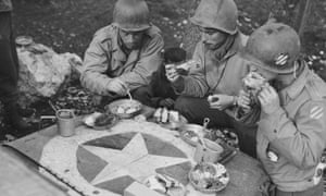 Soldiers eating Christmas dinner on the hood of a jeep during the second world war
