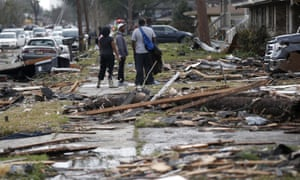People walk amongst debris from destroyed homes after a tornado tore through the eastern neighborhood in New Orleans Tuesday.