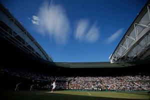 A brilliant blue sky above Centre Court as Ernest Gulbis serves to Novak Djokovic