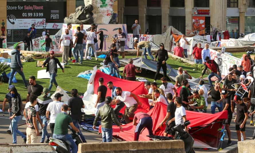 Protesters run as others destroy tents at a camp set up at an anti-government demonstration in central Beirut on Tuesday.