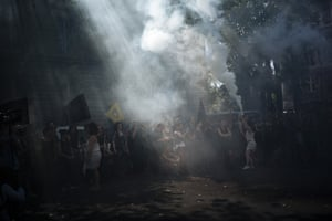 Extinction Rebellion activists hold a flare as they protest against Brazil's president Jair Bolsonaro and his failure to act and protect the Amazon rainforest.