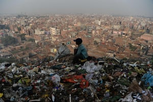 A young Indian ragpicker looks over New Delhi from a garbage dump at the Bhalswa landfill site