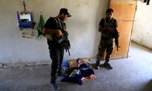 Iraqi forces inspect a house in west Mosul on Thursday.
