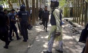 Bangladeshi policemen arrive near the scene of the attack in Sholakia
