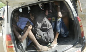 Garissa University students take shelter in a vehicle after fleeing al-Shabaab's latest attack