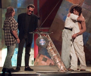 Former Van Halen bandmates David Lee Roth and Eddie Van Halen, right, embrace as they are reunited onstage at the MTV Video Music Awards in New York Wednesday, Sept. 4, 1996. Bandmates Michael Anthony, left, and Alex Van Halen are also present.