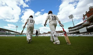 Rory Burns and Mark Stoneman of Surrey make their way on to the field to start their first innings against Lancashire.
